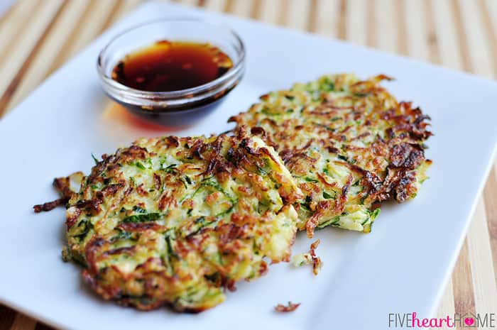 two fritters on a square plate with sauce