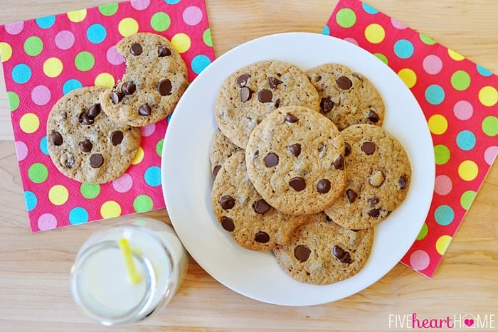 Aerial shot of chocolate chip cookies on a plate with milk and colorful napkins.