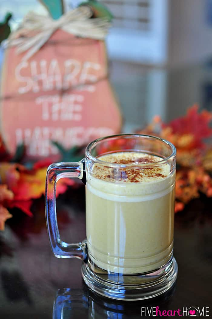 Warm Pumpkin Spice Drink in a Glass Mug with Fall Decorations in the Background