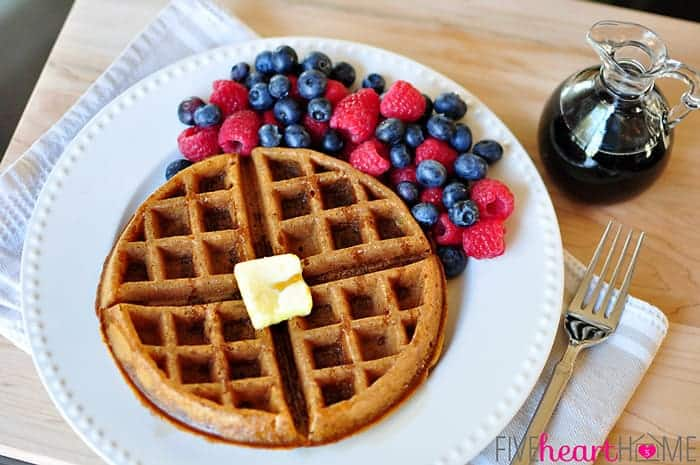 Whole Wheat Pumpkin Spice Waffles (Dairy-Free) on White Plate with Pat of Butter and Fresh Berries with a Pitcher of Syrup