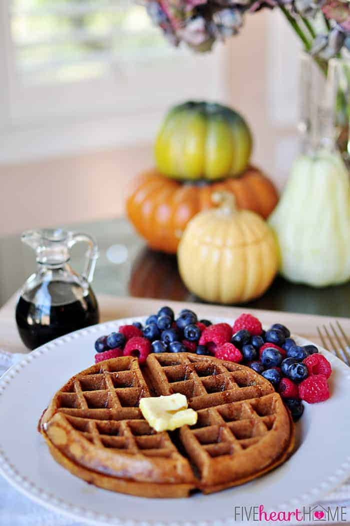 Whole Wheat Pumpkin Spice Waffles on White Plate with Fresh Berries and a Pitcher of Syrup with a Decorative Pumpkins in the Background