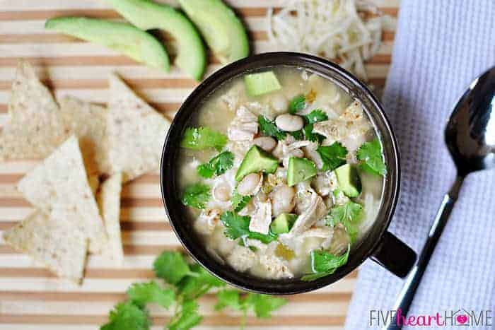 Aerial scene of bowl of White Bean Chicken Chili with tortilla chips, grated cheese, cilantro, and avocado slices on board