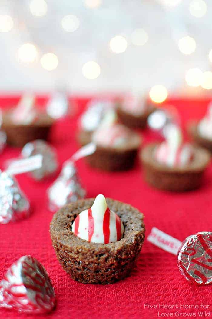 Christmas Brownie Bites on a red cloth with Candy Cane Hershey's Kisses sprinkled on table and twinkle lights in the background