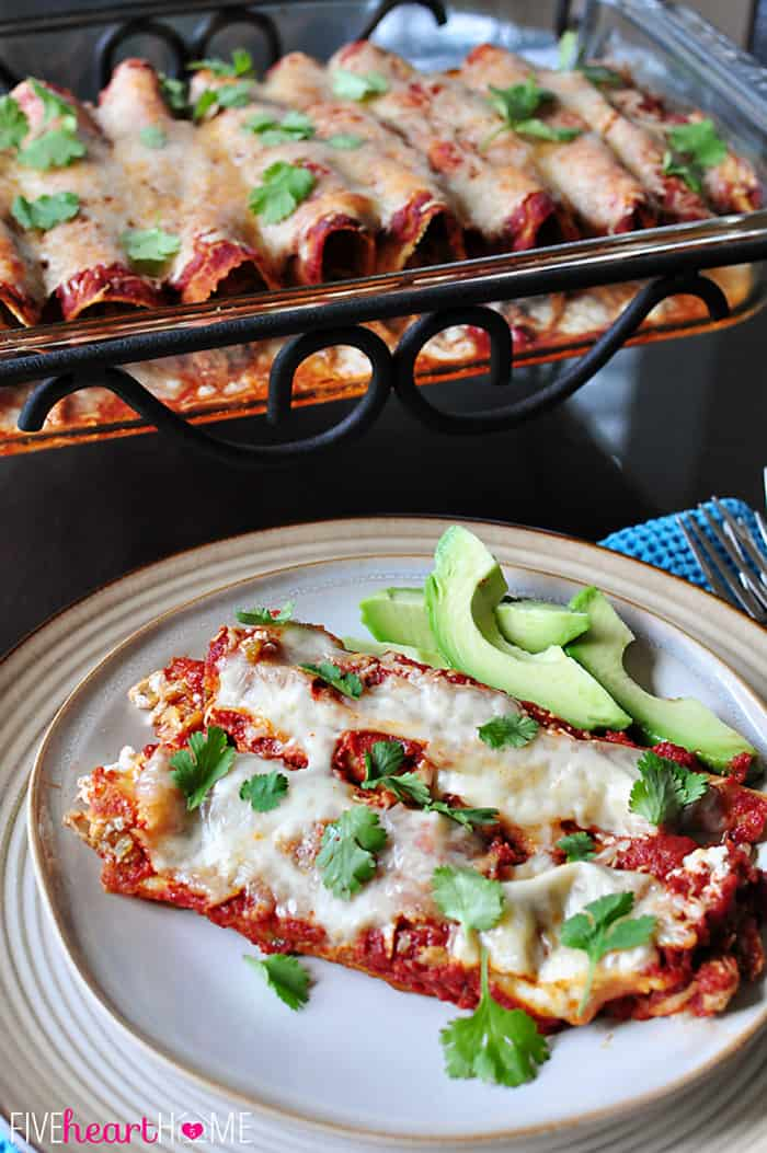 Creamy Chicken Enchiladas on plate garnished with avocado slices.