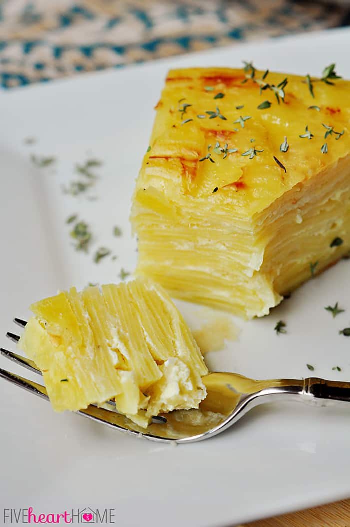 Scalloped Potato Flan with Gruyère and Garlic Bite on Silver Fork