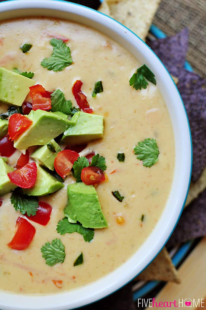 Aerial View of Cheddar and Sour Cream Queso in a Bowl with Garnish of Avocado, Tomato and Cilantro