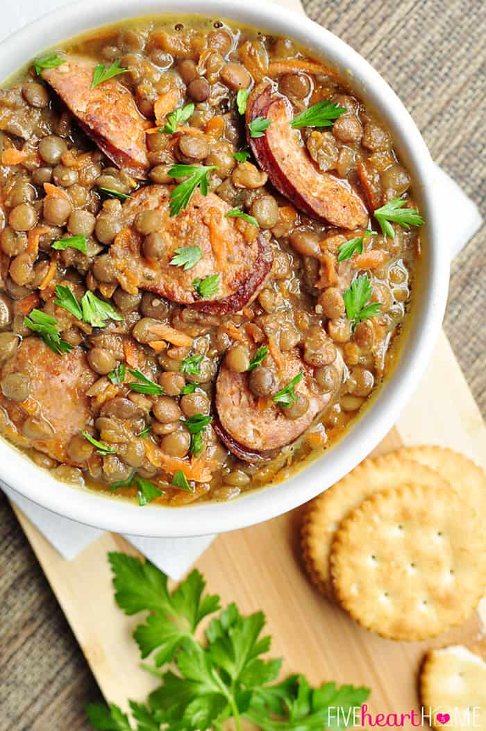 Slow Cooker German Lentil Soup in a White Bowl with Fresh Parsley Garnish