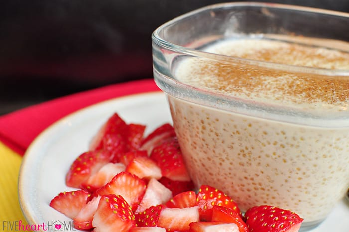 Quinoa Pudding in a clear glass dish with chopped strawberries on the side