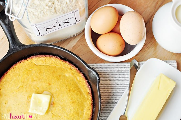 Aerial view of skillet of cornbread, jar of cornbread mix, bowl of brown eggs, and stick of butter