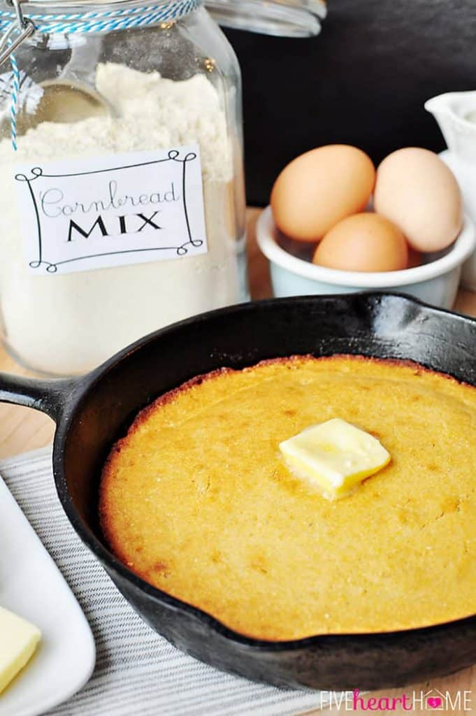 Cast iron skillet of cornbread with pat of butter on top