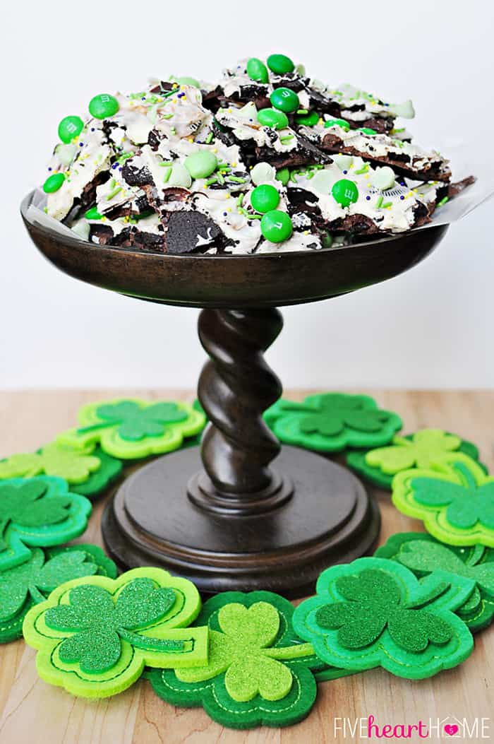 Leprechaun Bait on a pedestal with a ring of felt shamrocks on the table for the perfect St. Patrick's Day dessert