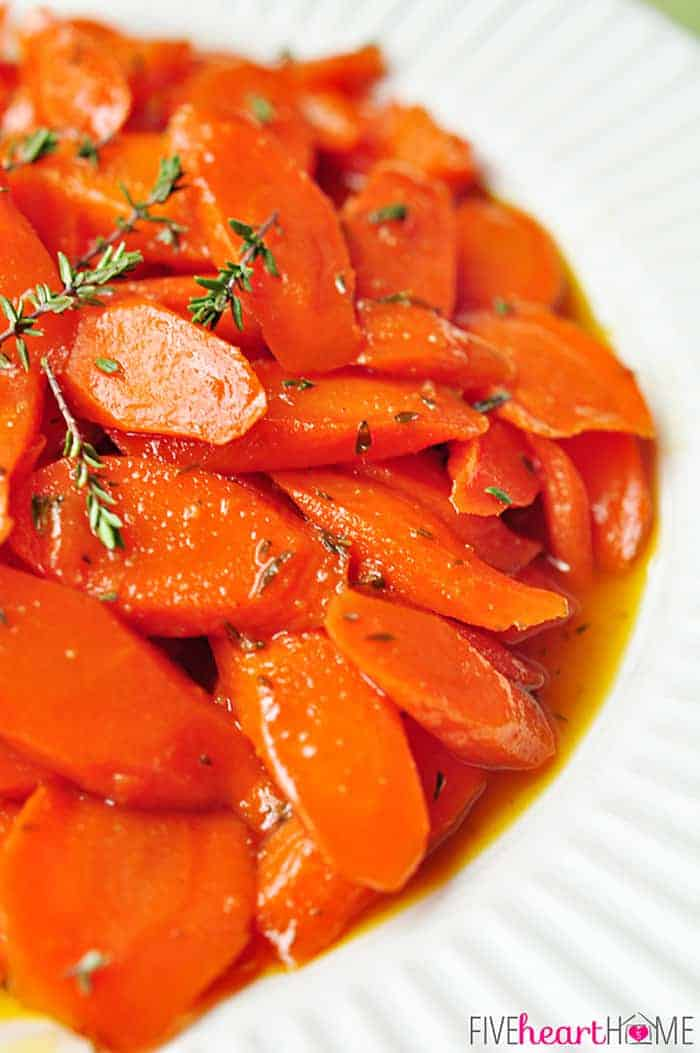 Close=up Of Honey-Glazed Carrots with Thyme and Lemon on White Plate