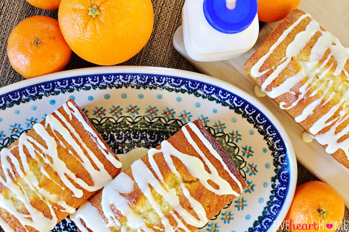 Aerial View of Orange Pound Cake Mini Loaves on Decorative Platter Surrounded by Fresh Oranges