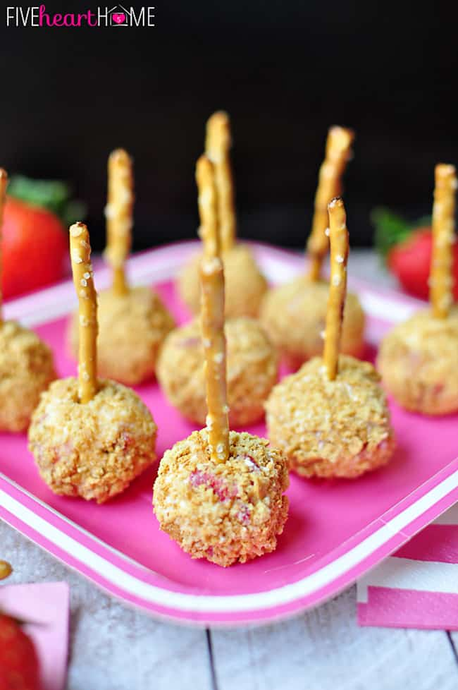 Strawberry Graham Cheese Ball Bites ~ cute little strawberry cheesecake balls rolled in graham cracker crumbs and skewered with a pretzel | FiveHeartHome.com