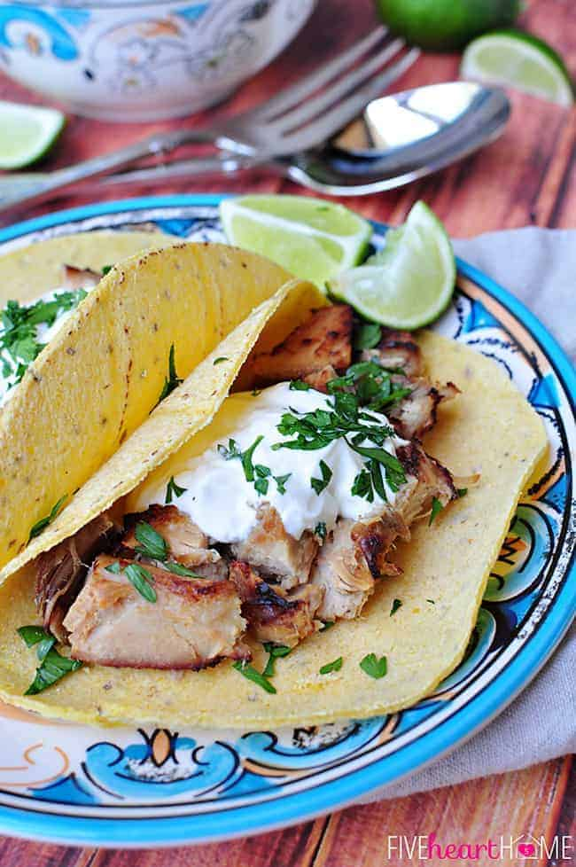 Slow Cooker Carnitas Tacos on Decorative Plate Topped with Sour Cream, Chopped Cilantro and a Lime Wedge