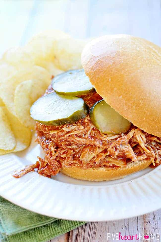 Slow Cooker Chicken Sloppy Joes with pickles on a plate with potato chips.