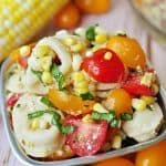 Tortellini Pasta Salad in a bowl with corn on the cob, colorful grape tomatoes, and basil leaf in background