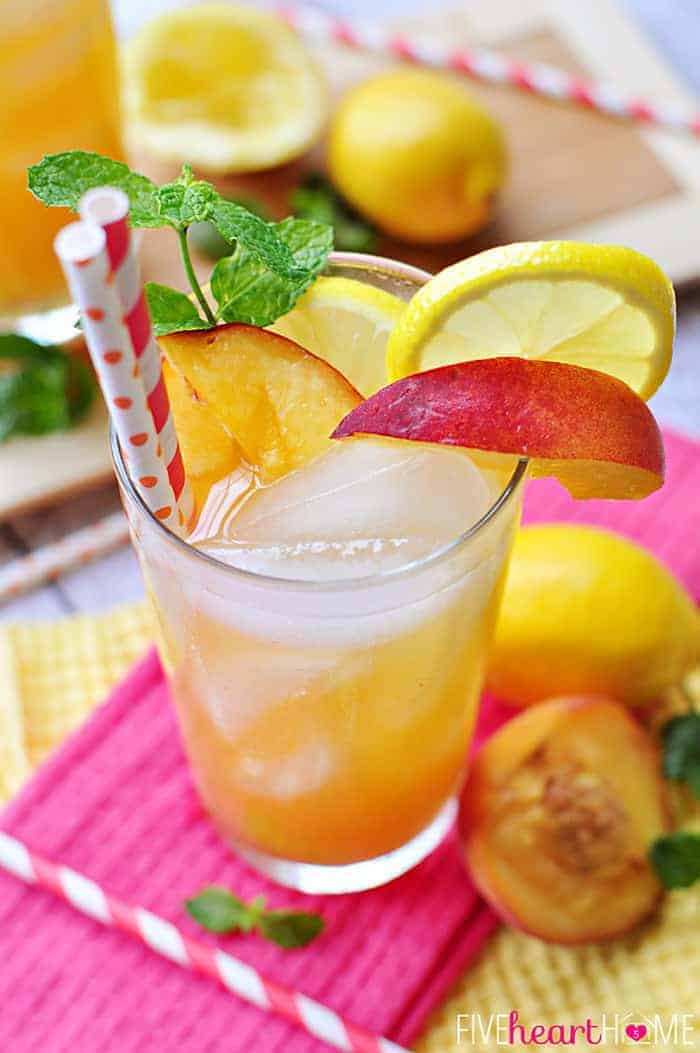 Close-Up of glass of Peach Lemonade loaded with garnishes and two colorful straws