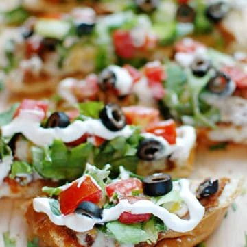 French Bread Taco Pizza ~ tacos meet pizza on an effortless French bread crust, with layers of refried beans, salsa, taco meat, cheese, lettuce, tomatoes, black olives, and sour cream! | FiveHeartHome.com