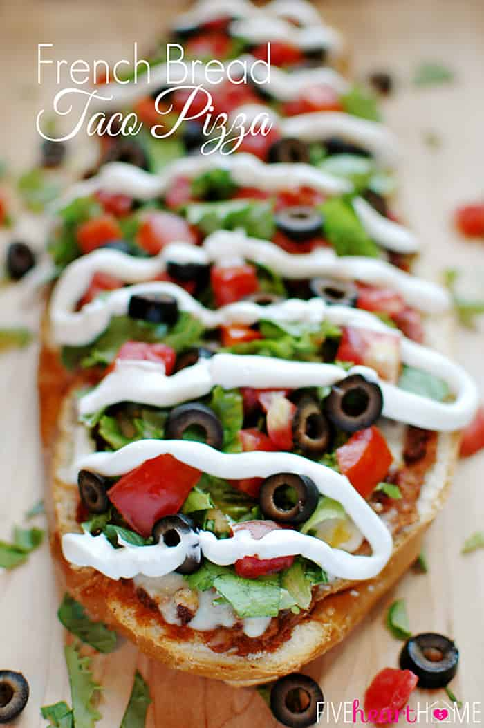 French Bread Taco Pizza ~ tacos meet pizza on an effortless French bread crust, with layers of refried beans, salsa, taco meat, cheese, lettuce, tomatoes, black olives, and sour cream! | FiveHeartHome.com via @fivehearthome