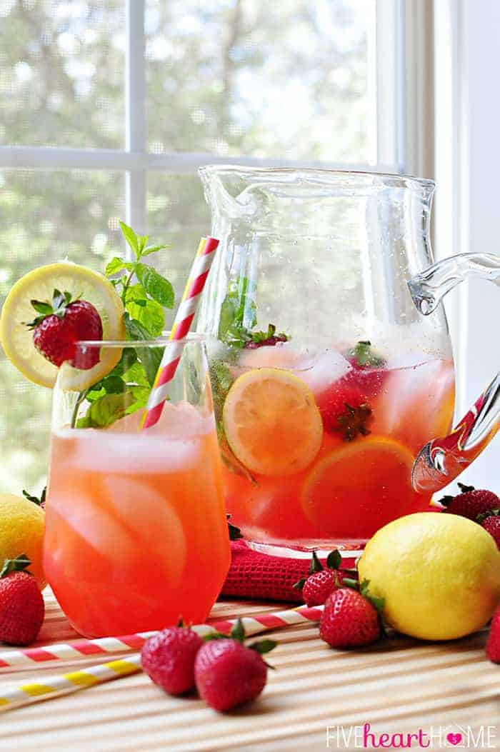 Strawberry Lemonade Mojitos {or} Faux-jitos in a Glass with Garnish of Strawberries, Lemon Slice and Mint Garnish and a Large Glass Pitcher