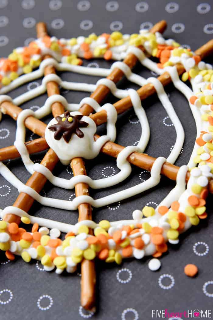 Pretzel Candy Spiderweb with orange, yellow, and white sprinkles and chocolate spider in the center