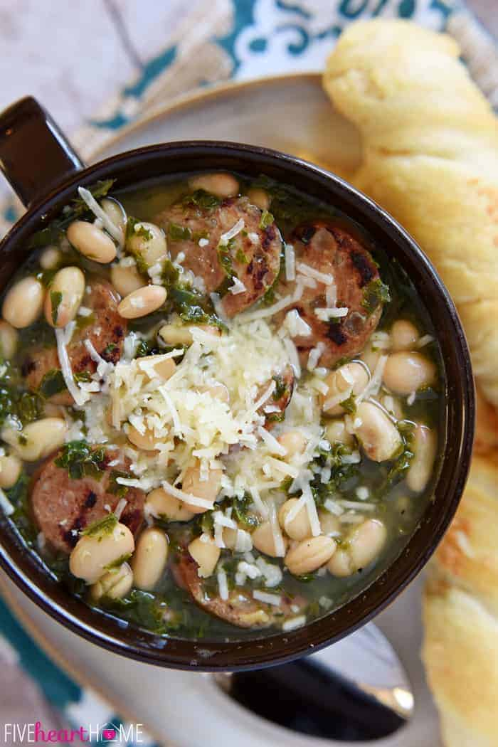 Close-up of soup showing sausage, white beans, kale, and parmesan cheese.