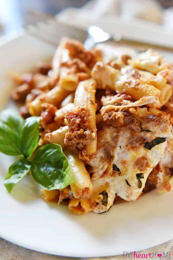Baked Ziti Served on White Plate with Fresh Basil Sprig for Garnish