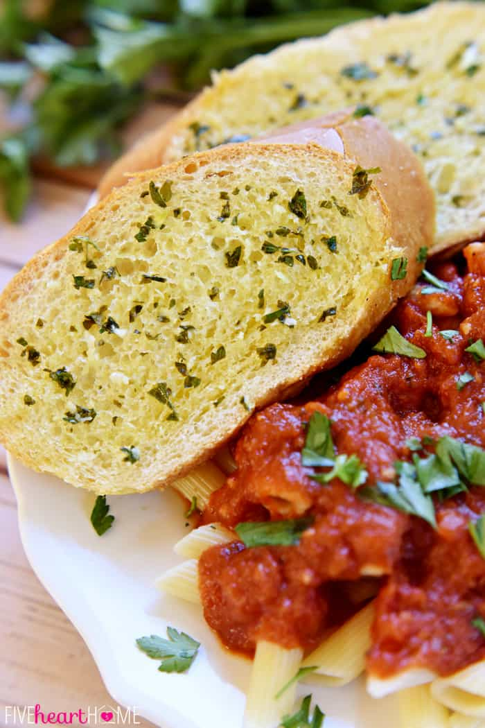 Garlic Bread with Fresh Garlic and Parsley Served Alongside Pasta