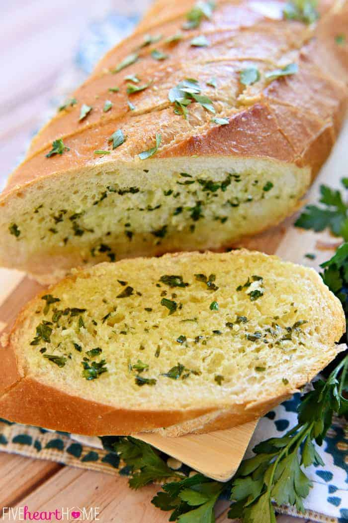 Slice of Garlic Bread with Fresh Garlic and Parsley on Decorative Tea Towel
