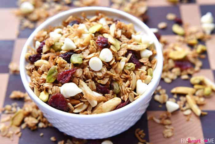 Gingerbread Granola with Cranberries, Pistachios, and White Chocolate Chips in White Bowl on Checkered Wood Table