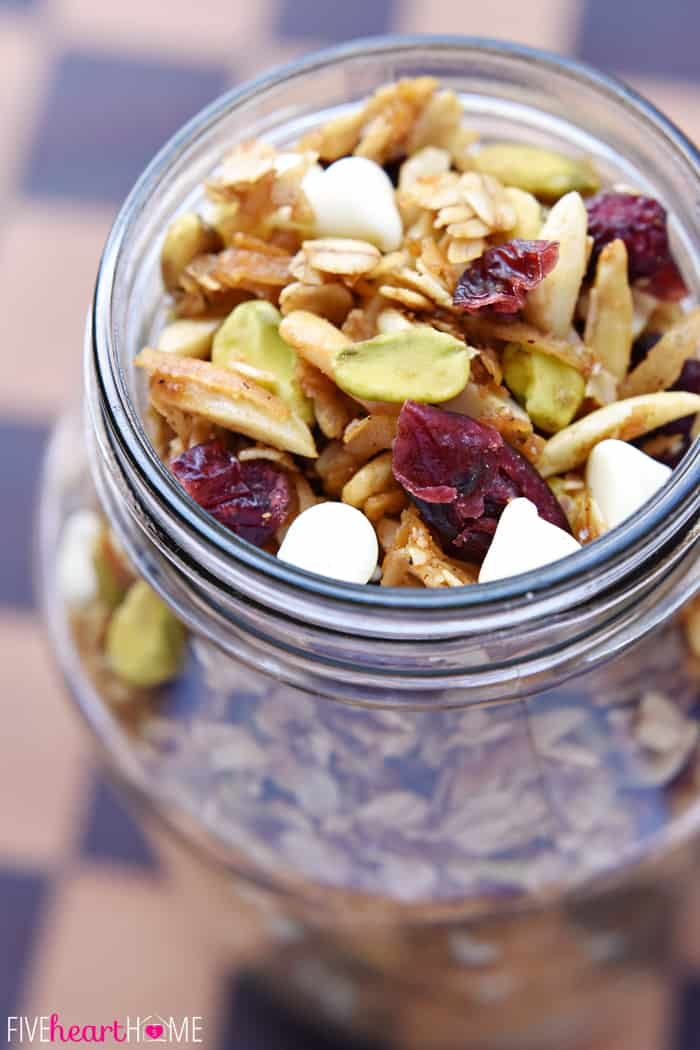 Close-Up of Gingerbread Granola with Cranberries, Pistachios, and White Chocolate Chips in a Glass Mason Jar