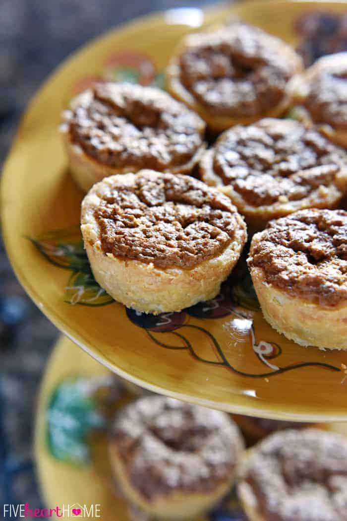 Mini Pecan Pies Piled on a Decorative Painted Plate Showcasing Crunchy Top and Flaky Crust