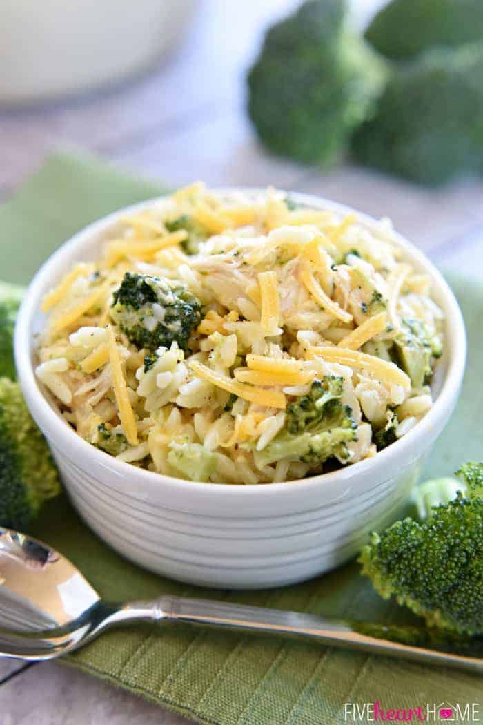 Broccoli Cheese Orzo with Chicken in White Bowl, Silver Spoon and Topped with Shredded Cheese