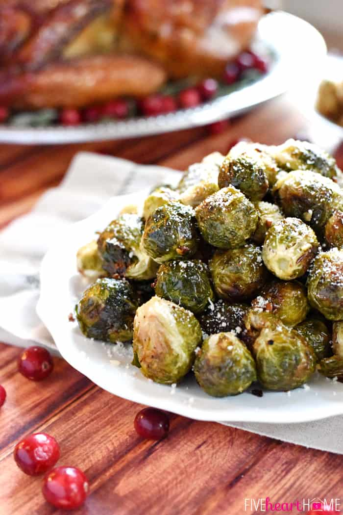 Roasted Brussels Sprouts with Parmesan Piled High on a White Scalloped Platter