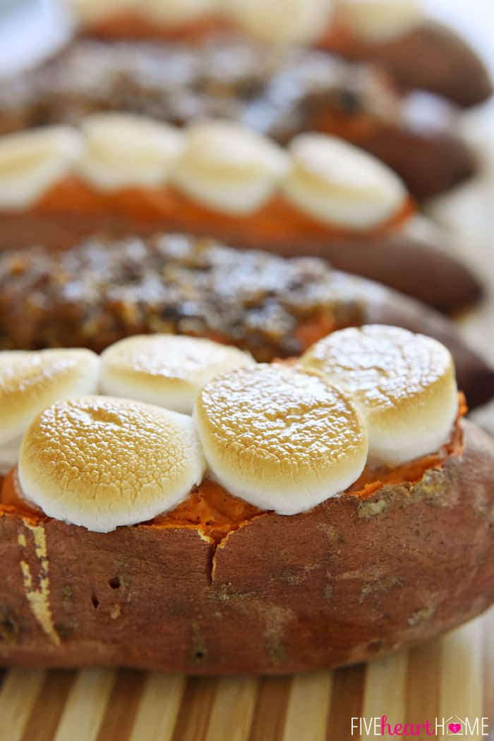 Twice-Baked Sweet Potatoes on wooden board topped with marshmallows and pecan streusel.