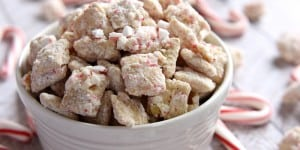 White Chocolate Peppermint Puppy Chow, AKA Muddy Buddies ~ incorporates Chex, white chocolate, crushed candy canes, and powdered sugar for a sweet holiday snack mix; this effortless recipe makes a big batch, perfect for sharing with friends and neighbors as a homemade food gift! | FiveHeartHome.com