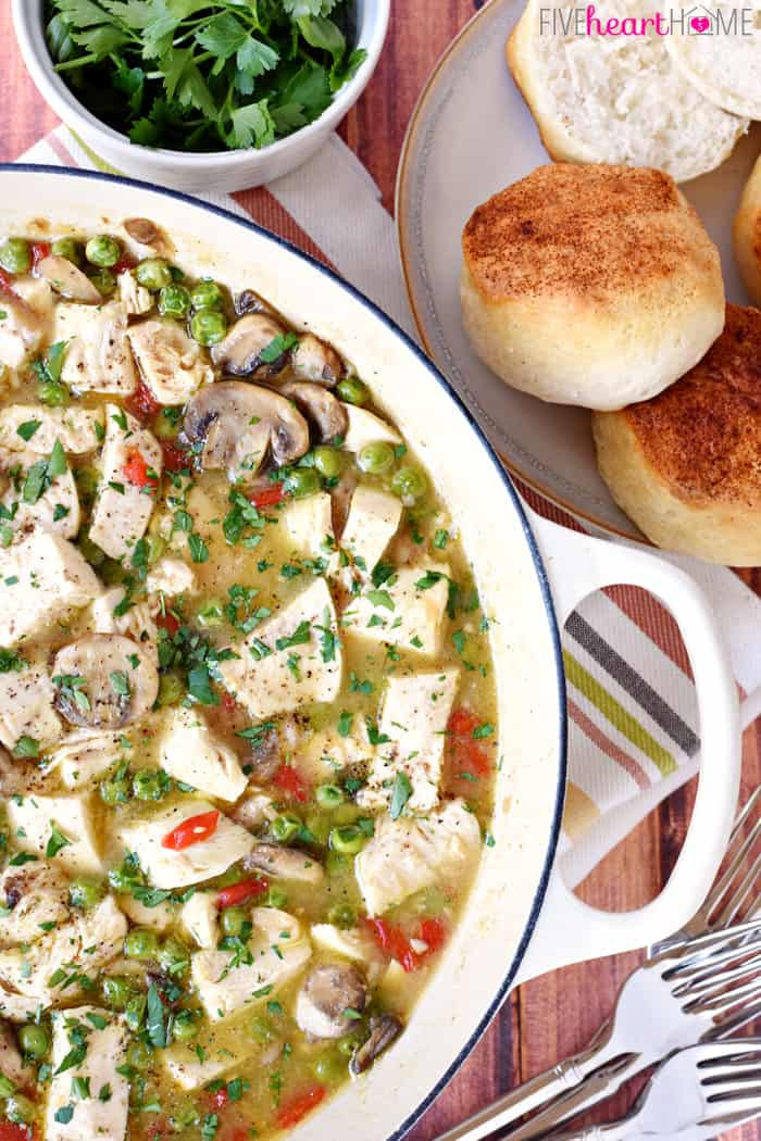 Chicken à la King ~ simple, classic dinner recipe featuring tender chicken breasts, garlicky mushrooms, sweet peas, zesty pimentos, and fresh parsley in a flavorful sauce served over warm, fluffy biscuits | FiveHeartHome.com