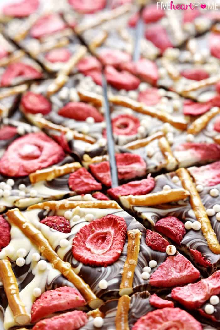 Close-up Showing semi-sweet and white chocolate, salty pretzels, tart strawberries, and festive sprinkles