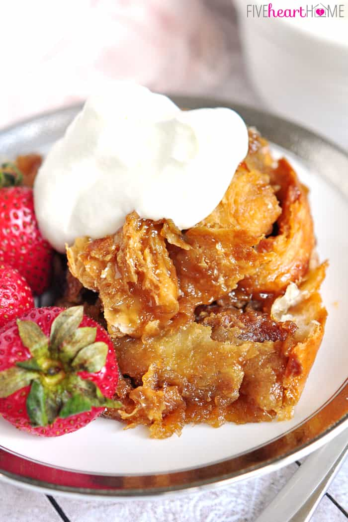 Easy Caramel Croissant Bread Pudding on Silver Rimmed Plate with Fresh Strawberries and Whipped Cream