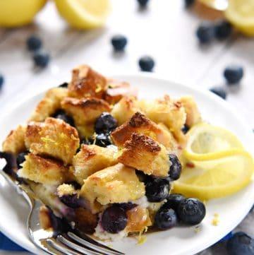 Lemon Blueberry Overnight Baked French Toast with Lemon Syrup on white plate.