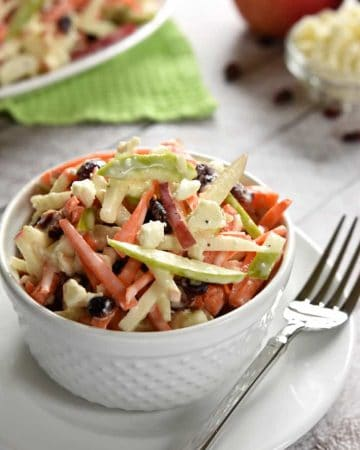Carrot Apple Slaw ~ with crunchy carrots, sweet and tart apples, dried cranberries, salty feta cheese, and a creamy dressing, this salad is a refreshingly sweet and savory side dish for summer! | FiveHeartHome.com