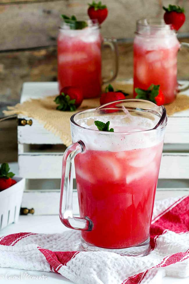 Strawberry Punch in a pitcher with glasses in background