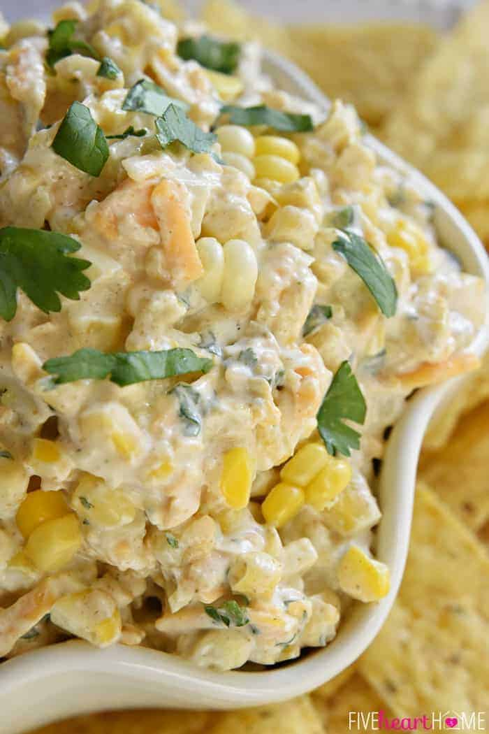 Close-up of Corn Dip in bowl with fresh corn, cheese, cilantro, jalapeños, and cumin.
