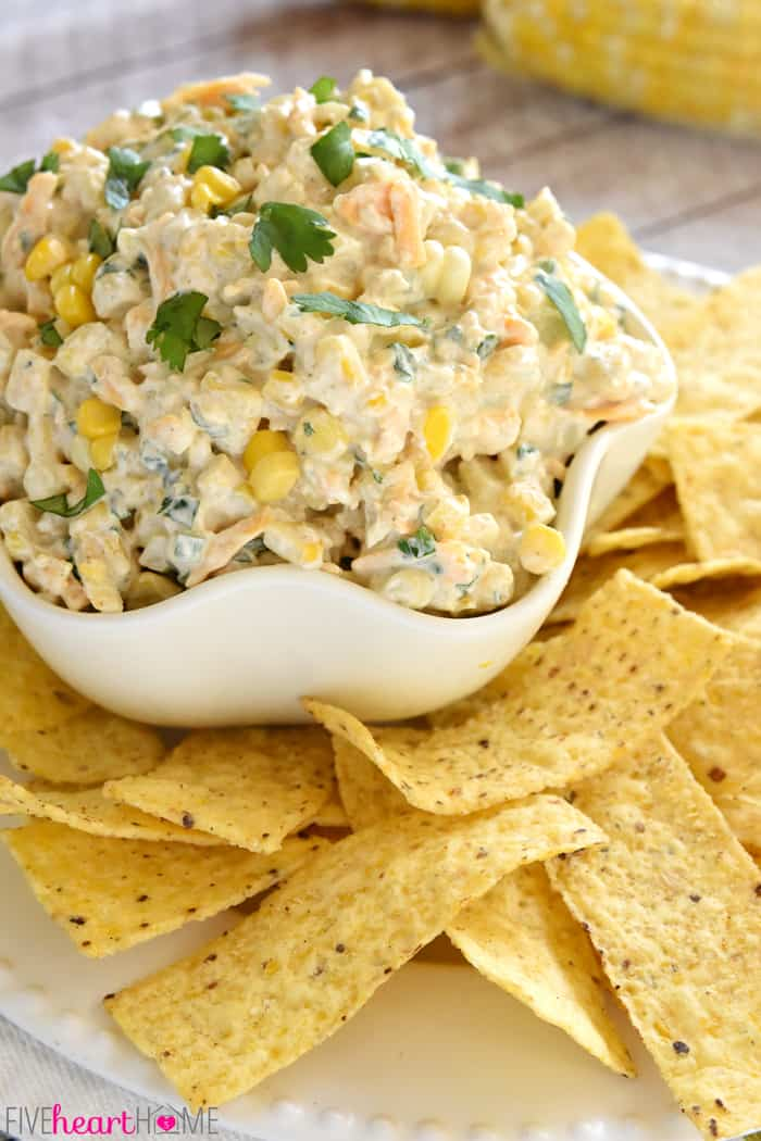 Corn Dip in a white serving bowl with tortilla chips.