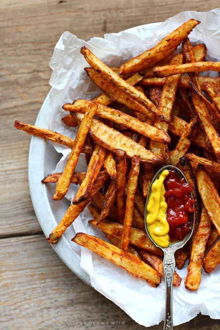 Baked Seasoned Fries ~ homemade French fries are coated with a delicious, spicy seasoning mix and then baked for a crispy, lightened-up side dish or snack! | LoveGrowsWild.com for FiveHeartHome.com via @fivehearthome