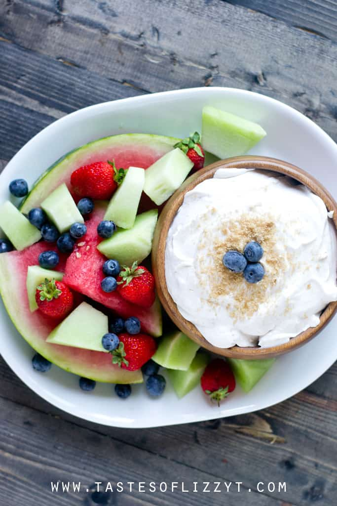 Aerial View of Brown Sugar Fruit Dip in a Wooden Bowl Surrounded by Fresh Fruit on a White Platter