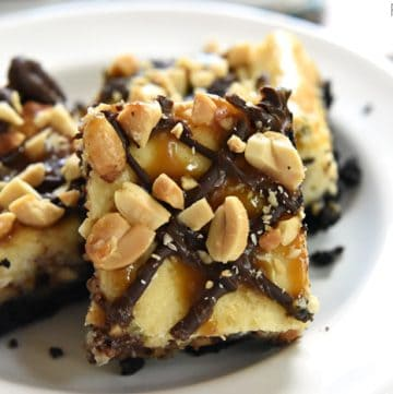 Snickers Cheesecake Bars ~ a crunchy Oreo crust is topped with a decadent layer of Snickers-studded cheesecake, drizzled with smooth chocolate and gooey caramel, and then sprinkled with salty chopped peanuts! | FiveHeartHome.com