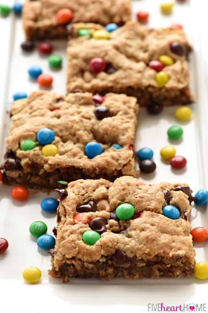 Monster Cookie Bars ~ loaded with chewy oats, decadent peanut butter, colorful M&Ms, chocolate chips, and peanut butter chips, this effortless batter whips up in no time! It's then spread in a large rimmed sheet pan for a BIG batch of bar cookies, perfect for sharing or serving at parties. Even better, you can customize these yummy cookies for various holidays by using seasonal M&Ms! | FiveHeartHome.com