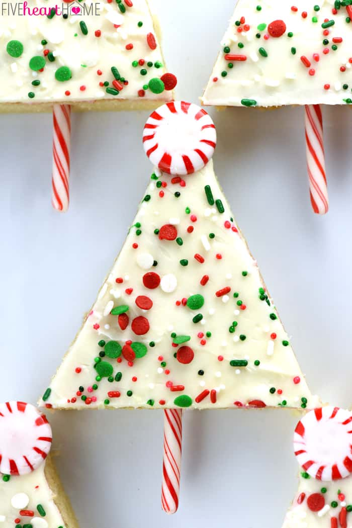 Christmas Tree Sheet Cake Pops ~ tender vanilla sheet cake is slathered in cream cheese frosting, showered with sprinkles, cut into triangles, and embellished with candy canes to make cute & festive treats...perfect for any holiday party or Christmas cookie platter! | FiveHeartHome.com